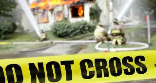 Firefighters at house fire, yellow tape © Frenzel/Shutterstock.com