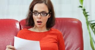 Shocked woman looking at document © bokan/Shutterstock.com