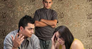 Worried couple with upset son in living room © CREATISTA/Shutterstock.com