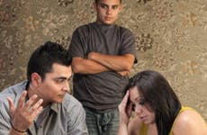 Worried couple with upset son in living room © CREATISTA/Shutterstock.com