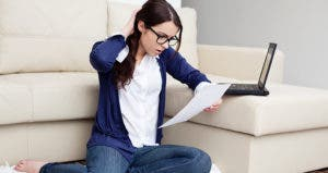Surprised young woman reading document in living room © baranq/Shutterstock.com