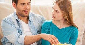 Man stealing popcorn from bowl © g-stockstudio/Shutterstock.com