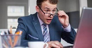 Shocked man at desk © Jakub Zak/Shutterstock.com