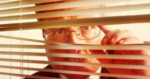 Man looking through window blinds © Suzanne Tucker/Shutterstock.com