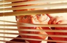 Man looking through window blinds © Suzanne Tucker/Shutterstock.com