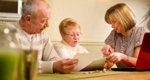 Seniors talking over paperwork at table © iStock