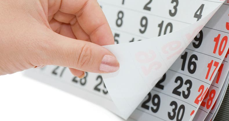 woman flipping page of calendar closeup mst