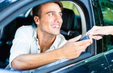 Man in drivers seat taking car keys from saleswoman © iStock