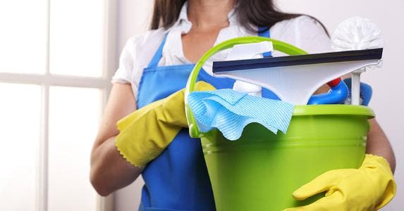 Housemaid holding pail of cleaning materials © iStock