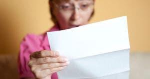 Woman shocked holding bill © iStock