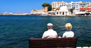 Senior couple sitting on a bench in overseas country © iStock