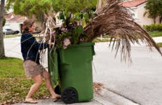 Woman putting out recycle bin full of plant waste © iStock