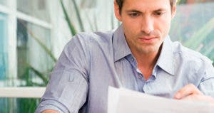 Serious man looking over paperwork  © iStock