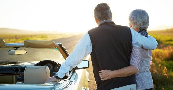 Mature couple standing next to a convertible car, enjoying the scenery © iStock