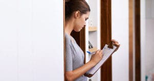 Woman leaning against doorframe with clipboard, writing © iStock