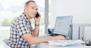 Man using phone while on computer © iStock