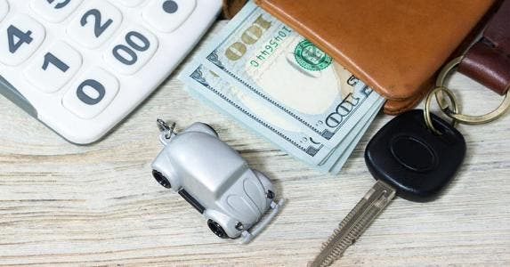 Toy car, money, keys and calculator on a table © iStock
