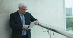 Senior businessman browing on mobile table in office balcony © iStock