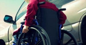 Woman in wheelchair, going to drivers seat of car © iStock