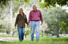 Senior couple walking under tree cover | Stevecoleimages/Vetta/Getty Images