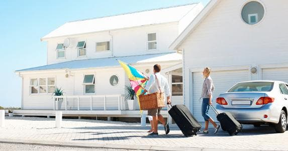 Couple taking luggage into vacation home on beach © iStock