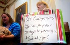 Woman holding sign protesting oil companies in Oklahoma State Capital | J Pat Carter/Getty Images