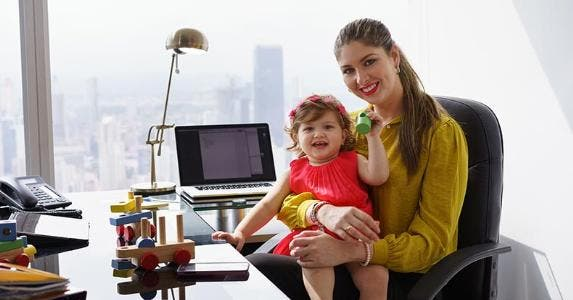 Mother holding her child in lap at desk © Diego Cervo/Shutterstock.com