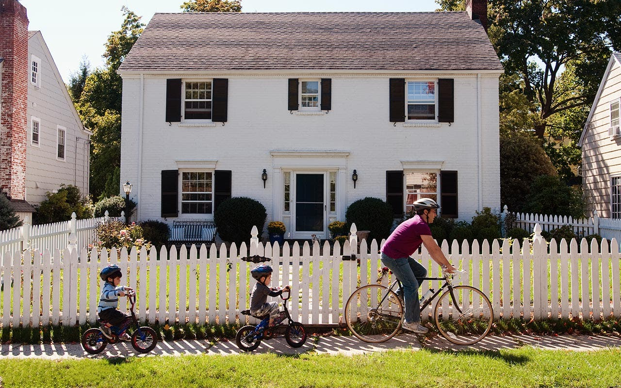 Father and two children riding bicycles in front of a house