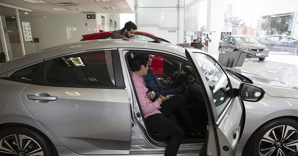 Man checking out new car in dealership showroom