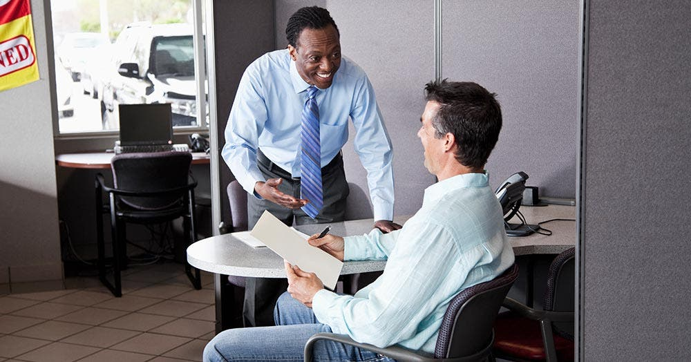 Car dealer talking to buyer at desk
