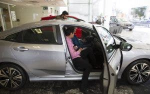 Man looking at a car inside the dealer showroom