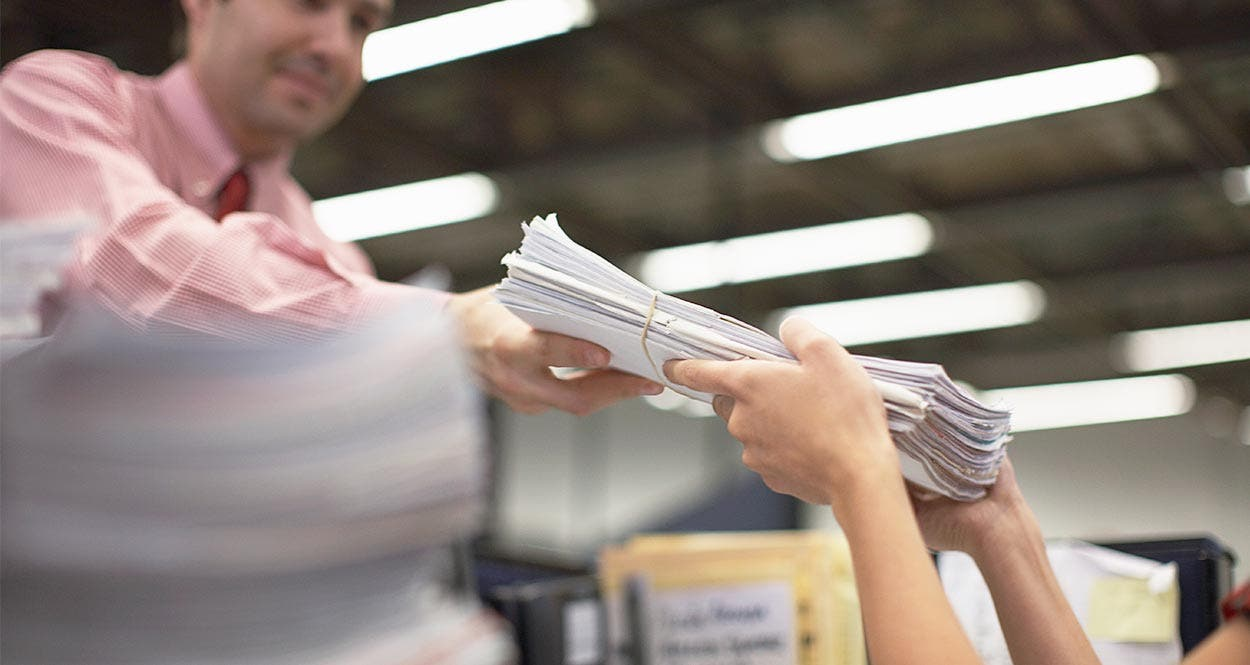 Man handing stack of files to woman