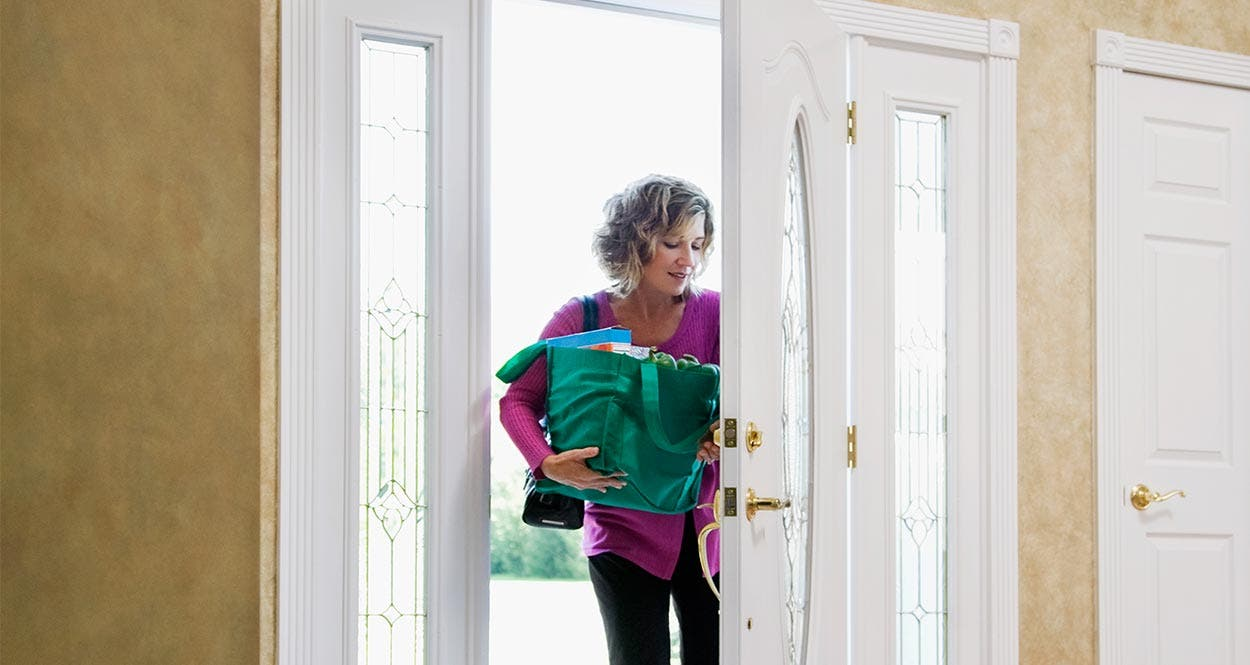 Woman stepping through front door