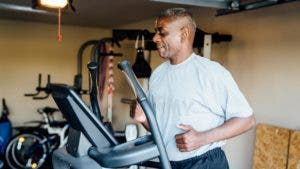 Veteran man running on treadmill inside garage