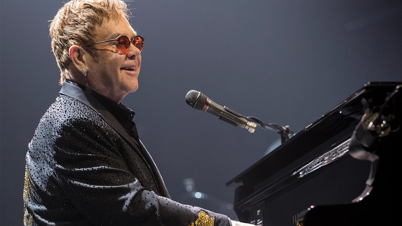 Elton John plays piano