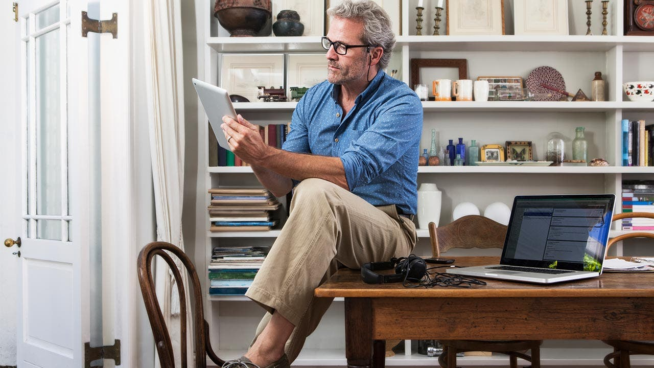 Man sitting on table and looking at tablet