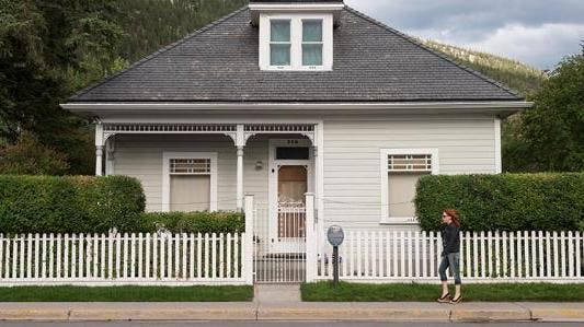 Woman walking by a house | John Elk III/Getty Images