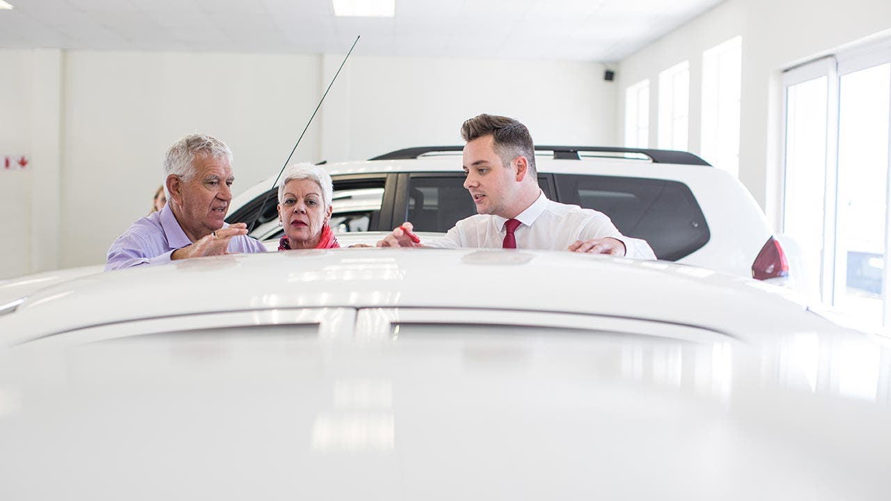 Three people looking at a car in the dealership