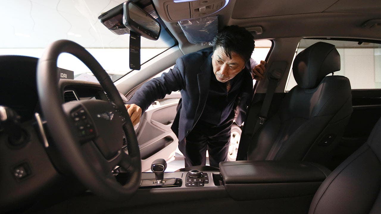 Man leaning into car looking at dashboard