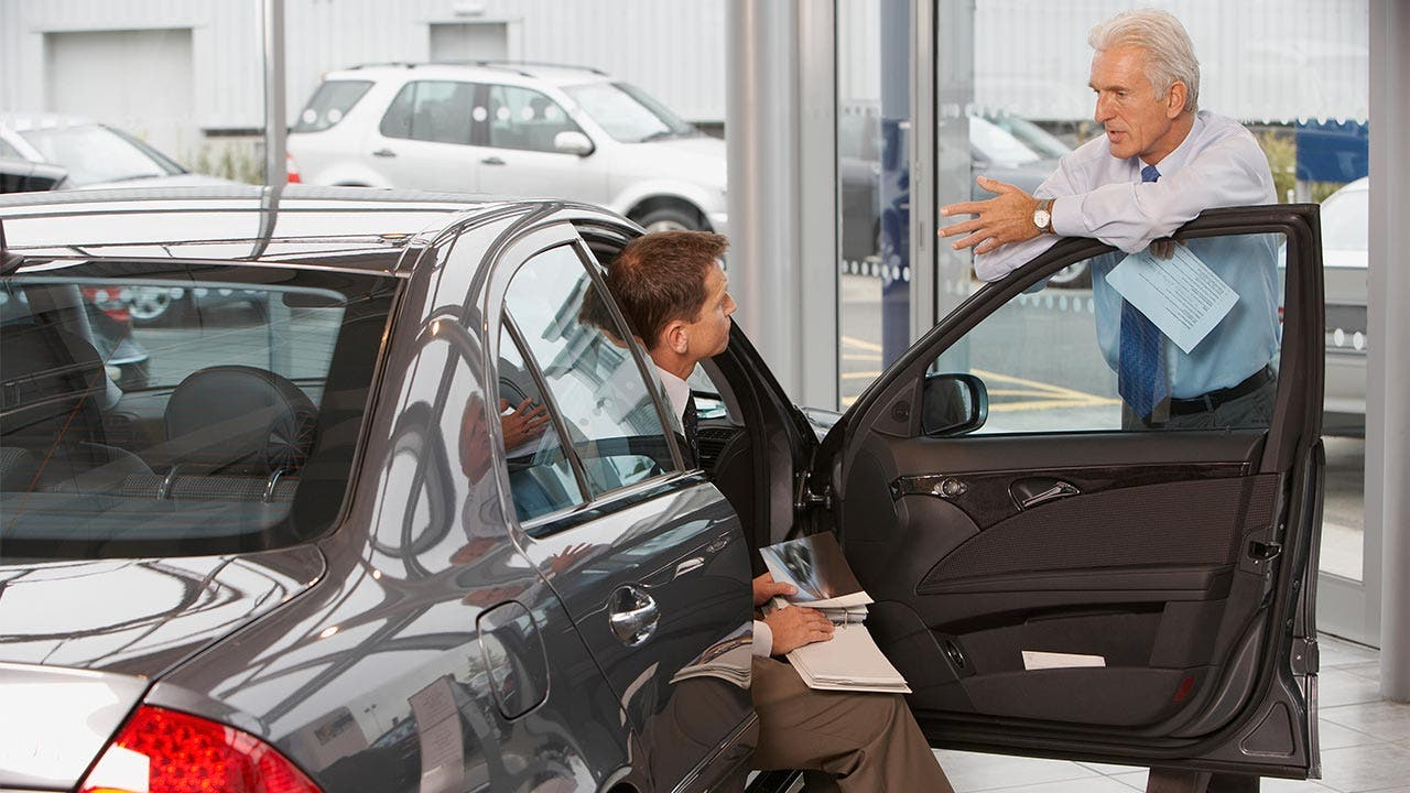 Car salesman talking to potential buyer seated in car