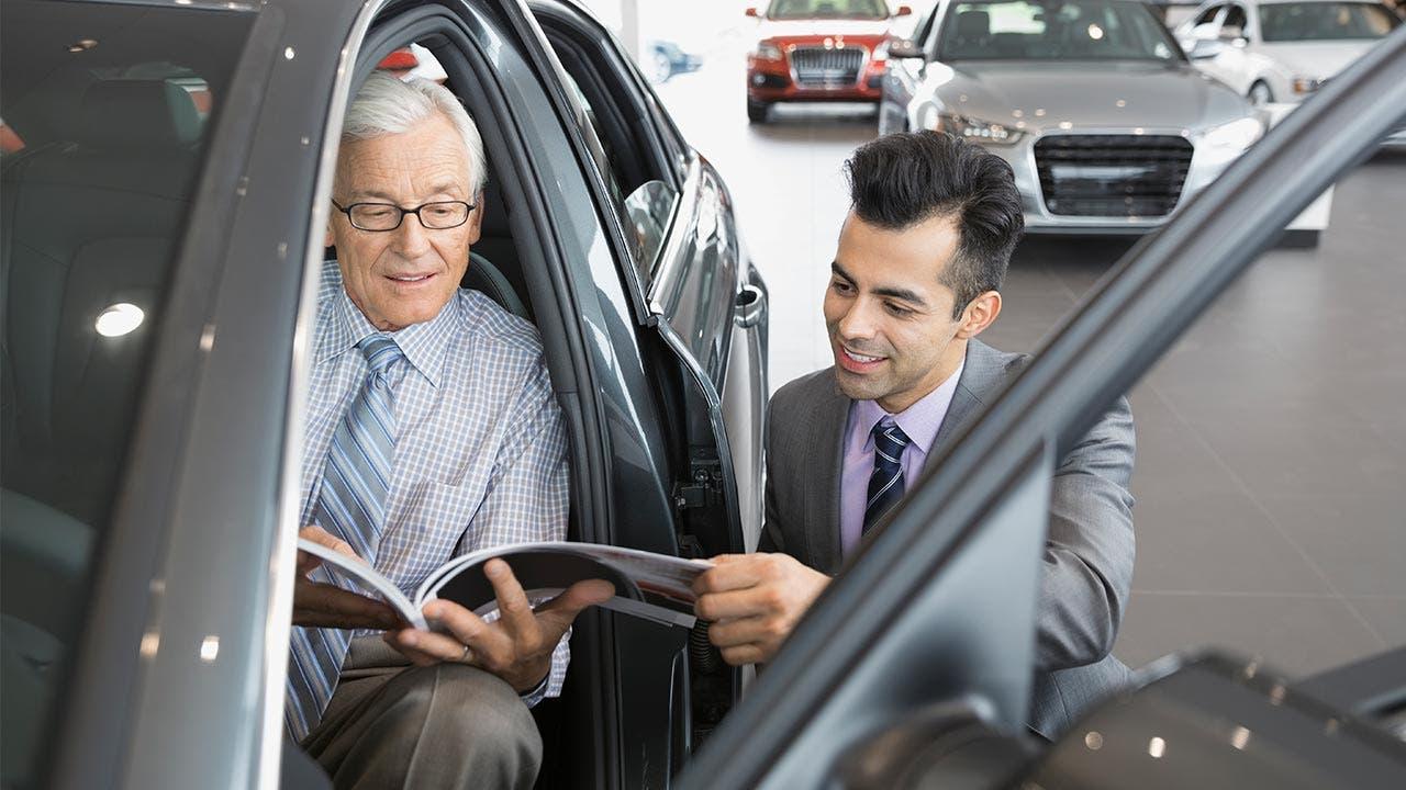 Car salesman talking to man seated inside car in showroom