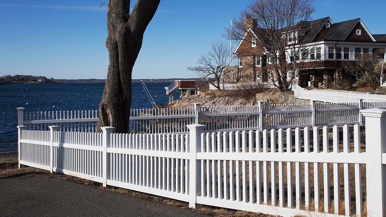 White picket fence around a waterfront home