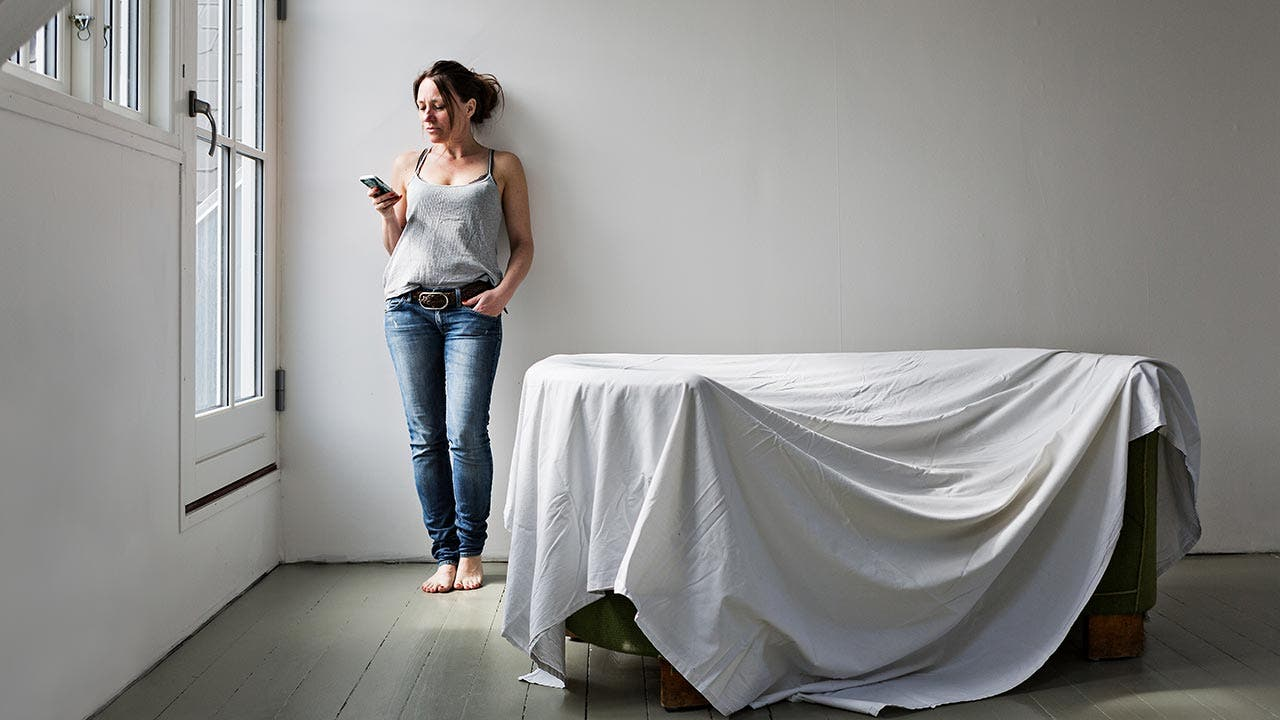 Woman texting in empty home