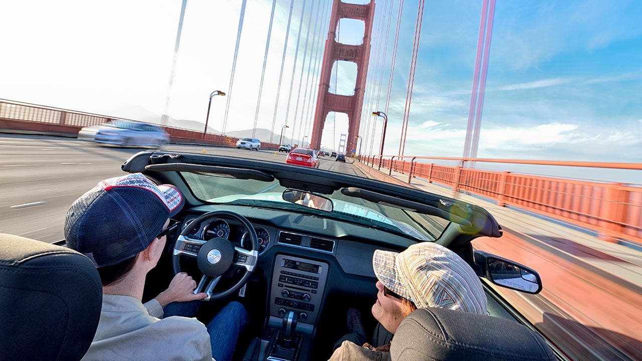 Couple driving in their convertible through the San Francisco bridge