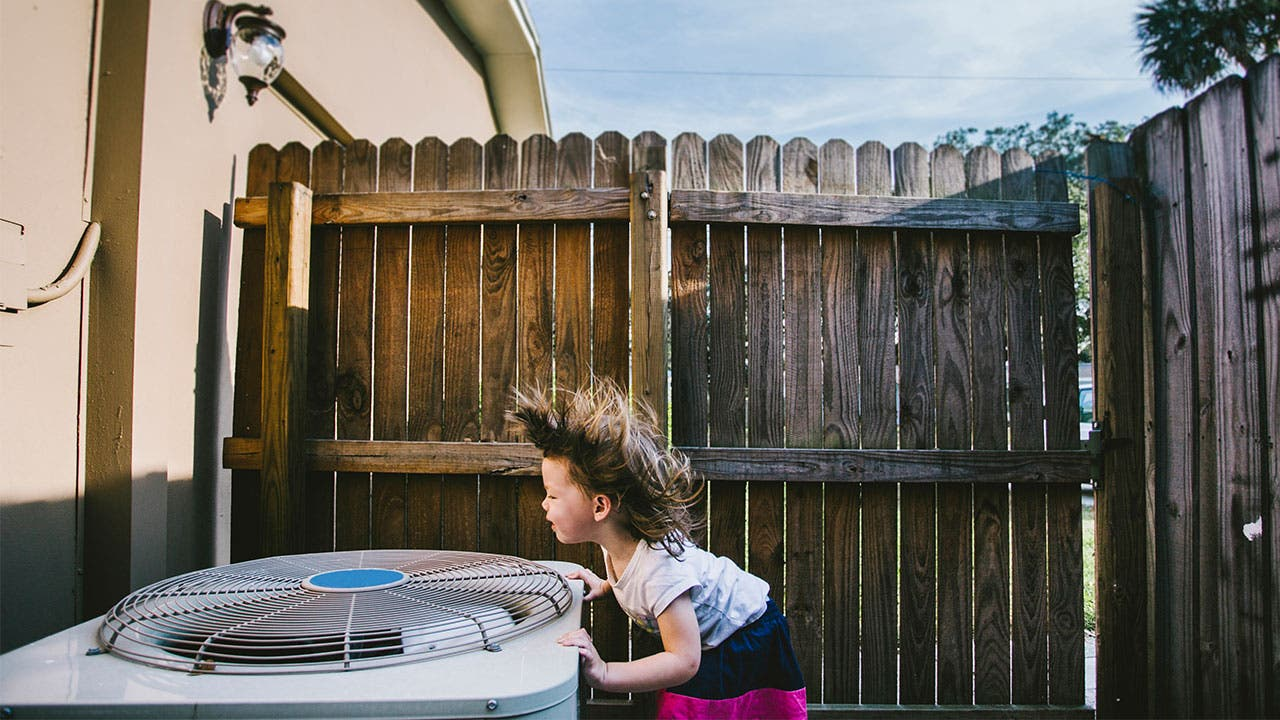 Kid cooling off over an AC unit