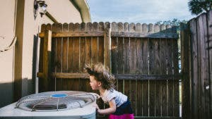 Child cooling off over an AC unit