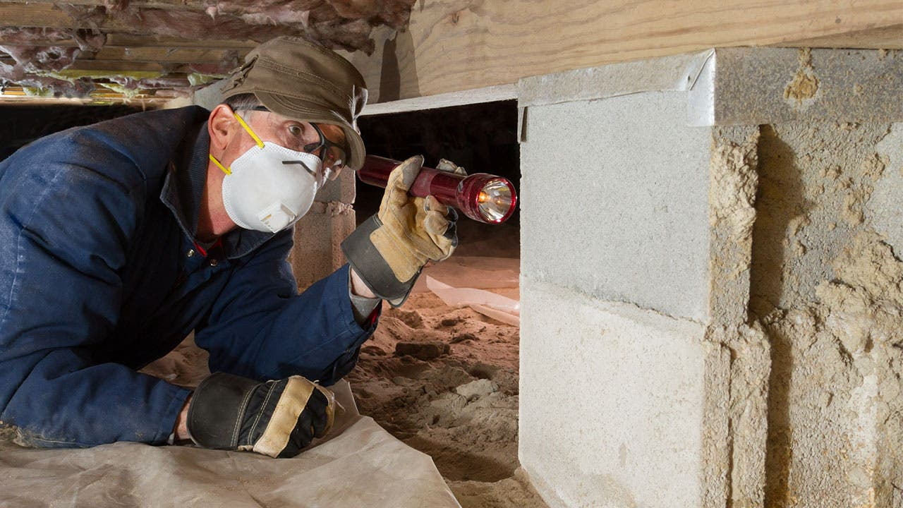 Home inspector looking in crawl space