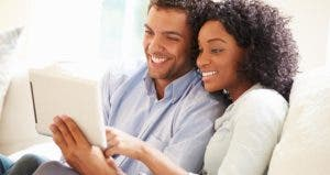 Couple sitting on white couch, browsing tablet computer | Monkey Business Images/Shutterstock.com