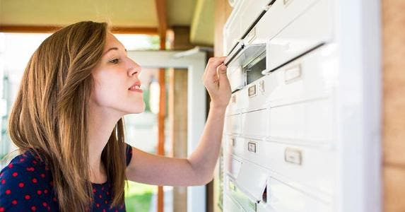 Woman checking her apartment mailbox | l i g h t p o e t/Shutterstock.com