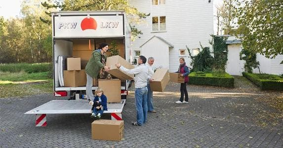 Group taking boxes off of the moving truck | Westend61/Getty Images